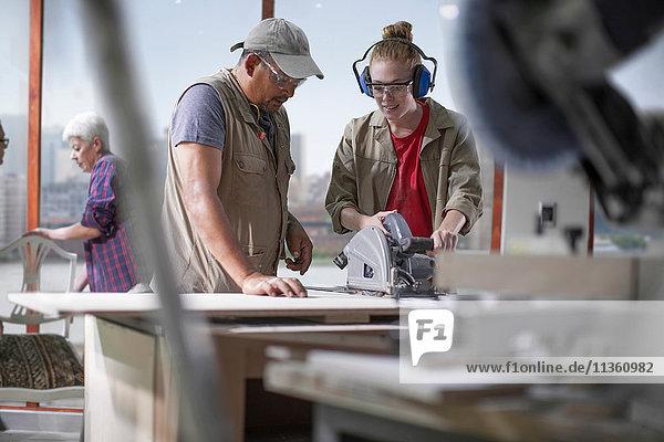 Tischlerlehrling lernt den Umgang mit der Motorsäge in einer Möbelwerkstatt
