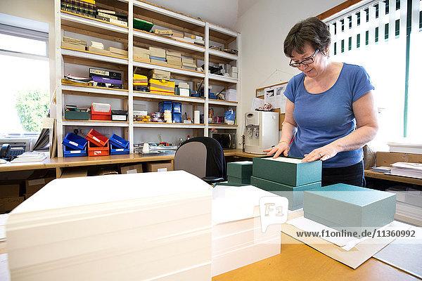 Arbeitnehmerin packt Auftrag in Pappkarton in Druckereiwerkstatt