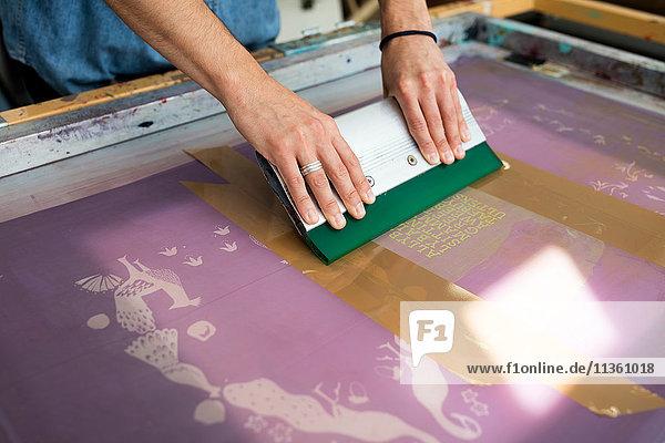 Hände eines jungen männlichen Druckers beim Rakeln im Druckmaschinenstudio