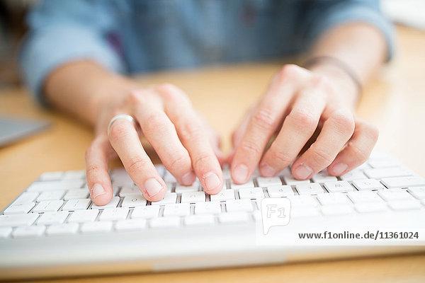 Nahaufnahme eines männlichen Designers beim Tippen auf der Computertastatur im Druckmaschinenstudio