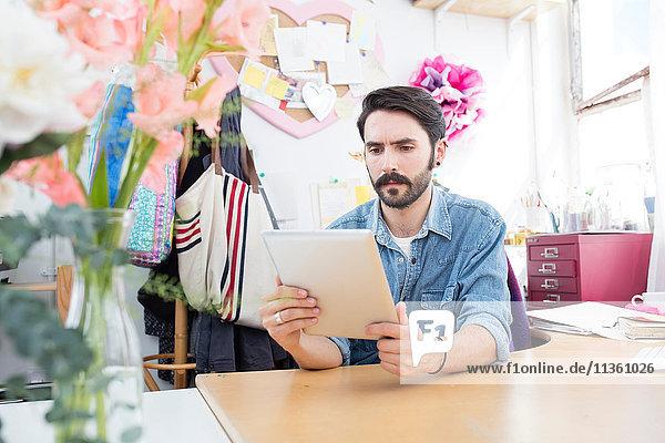 Junger männlicher Designer liest digitale Tablette im Druckmaschinenstudio