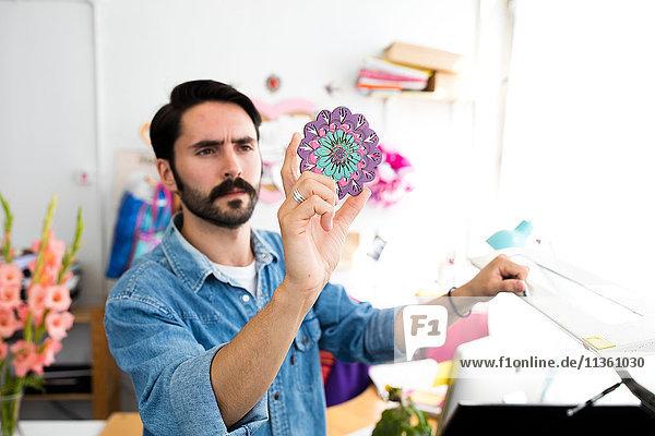 Junger männlicher Designer hält Rundschreiben im Druckmaschinen-Atelier hoch