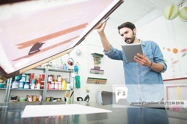 Männlicher Drucker bereitet Papier und Siebdruck im Druckmaschinenstudio vor