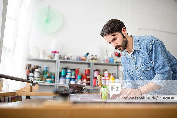 Männlicher Drucker  der im Druckmaschinenstudio grüne Farbe auf Siebdruck aufträgt