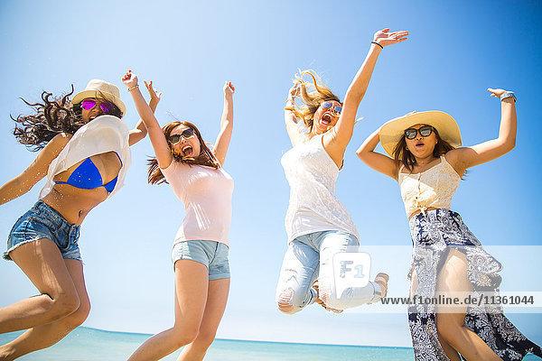 Vier erwachsene Freundinnen springen am Strand in die Luft  Malibu  Kalifornien  USA