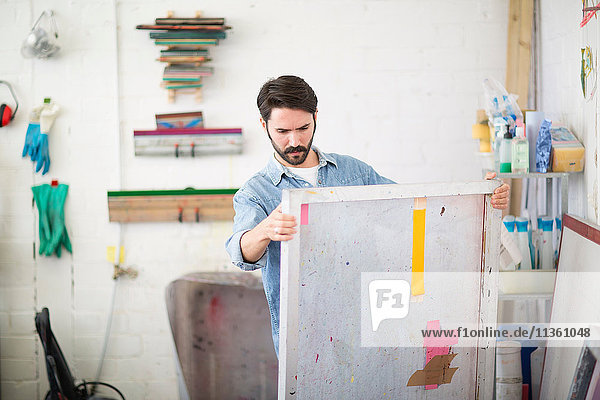 Junger männlicher Drucker betrachtet Leinwand im Druckmaschinen-Atelier