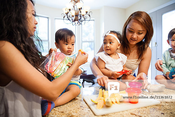 Women feeding baby son and daughter fruit on kitchen counter