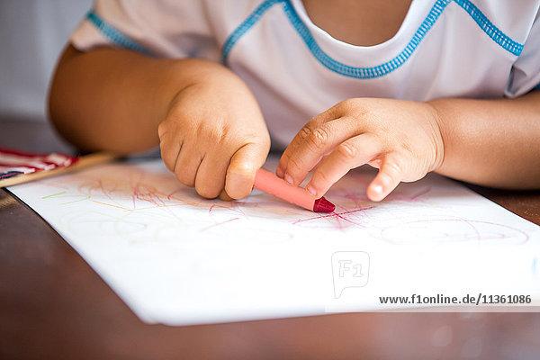 Nahaufnahme der Hände von kleinen Jungen Buntstiftzeichnung am Esstisch