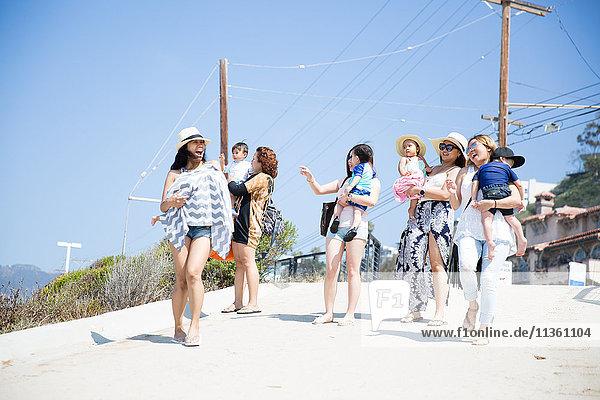 Vier erwachsene Freundinnen und ihre Babys spazieren am Strand entlang  Malibu  Kalifornien  USA