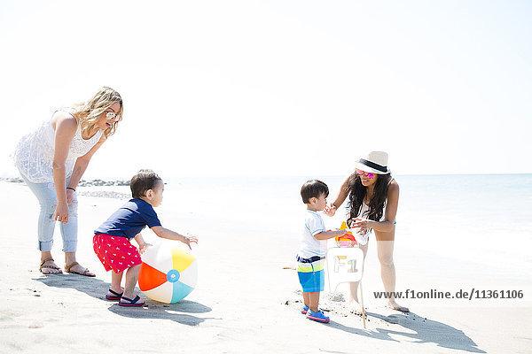 Zwei Mütter und kleine Söhne spielen mit Beachball und Windrädern am Strand  Malibu  Kalifornien  USA