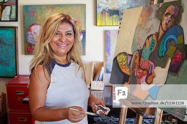Künstler malt Kunstwerke auf Leinwand  schaut lächelnd in die Kamera