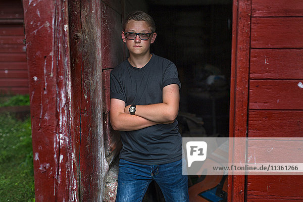 Portrait of teenage boy wearing tinted eyeglasses leaning against shed doorway