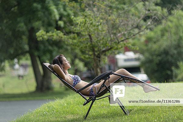 Teenagermädchen beim Sonnenbaden auf einer Sonnenliege im Garten