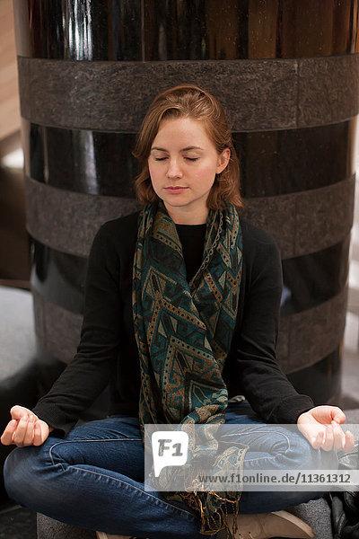 Frau sitzt im Schneidersitz und meditiert