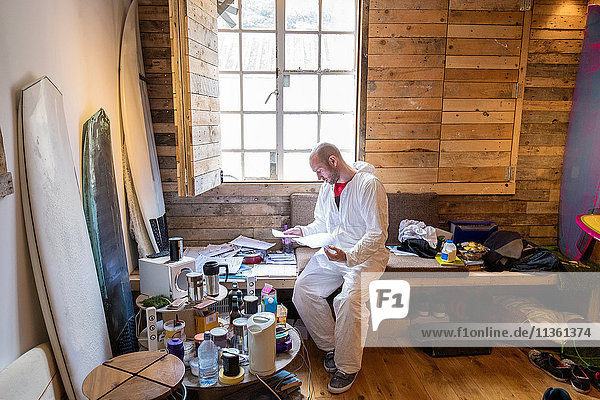 Männlicher Schreiner liest Papiere in der Werkstatt eines Surfbrettbauers