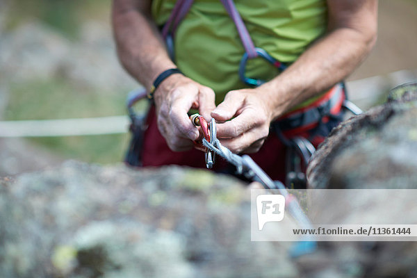 Cropped view of rock climber preparing climbing rope