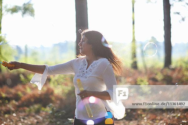 Frau im Wald macht Seifenblasen mit dem Seifenblasen-Stab