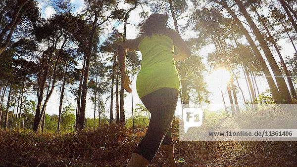 Rückansicht einer Frau  die im Wald joggt