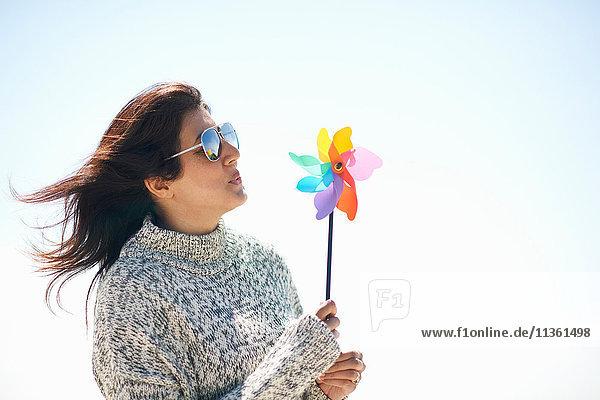 Woman wearing sunglasses holding pinwheel