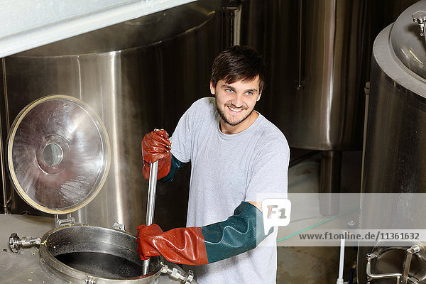 Worker in brewery  adding hops to brew kettle