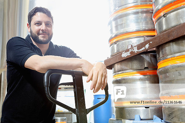 Portrait of worker in brewery organising beer barrels for delivery