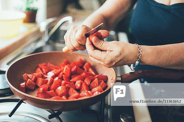 Schrägansicht einer Frau  die Tomaten in einen Kochtopf schneidet