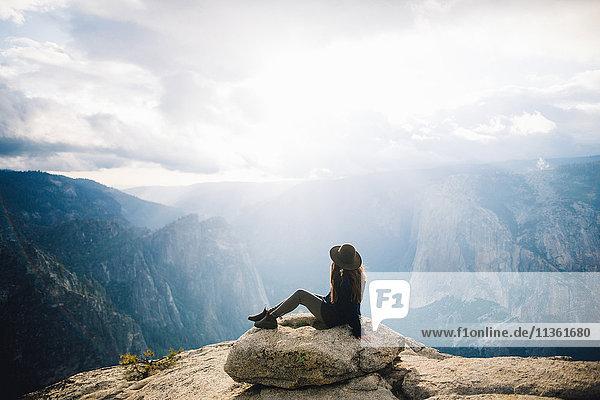 Junge Frau sitzt auf dem Gipfel eines Berges mit Blick auf den Yosemite National Park  Kalifornien  USA