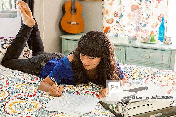 Junge Frau auf dem Bett liegend  Schreibmaschine benutzend  Notizen schreibend