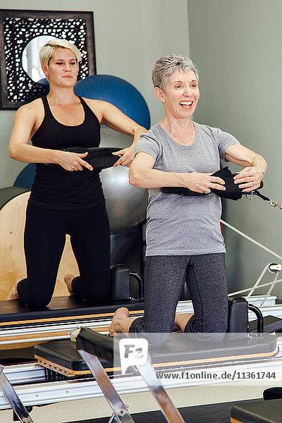 Frauen im Fitnessstudio mit Pilates-Reformer lächelnd