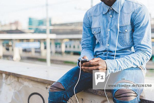 Beschnittene Ansicht des Mannes mit Kopfhörer über Smartphone  Mailand  Italien