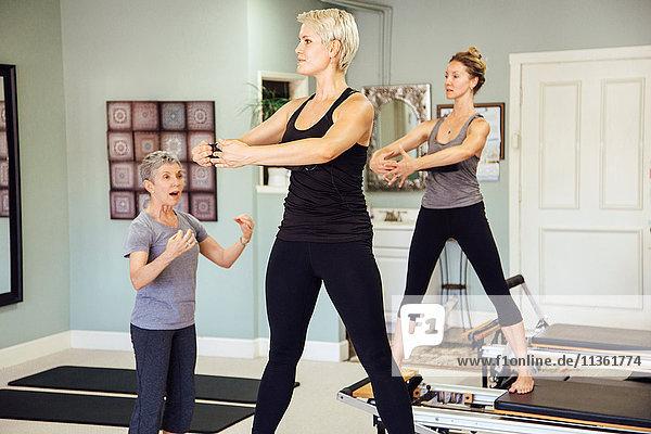 Women in gym using pilates reformer