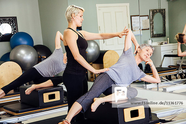Personal trainer teaching pilates in gym