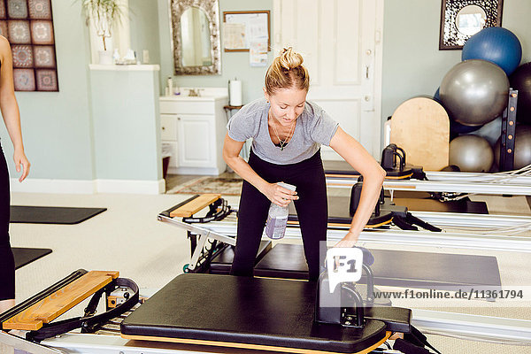 Women in gym cleaning pilates reformer
