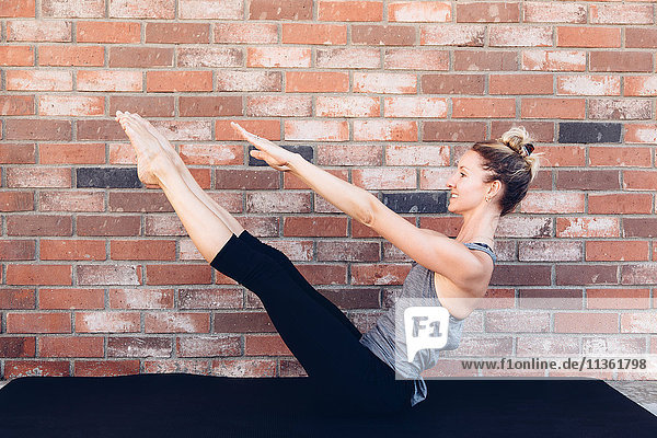 Side view of woman doing stretching exercise