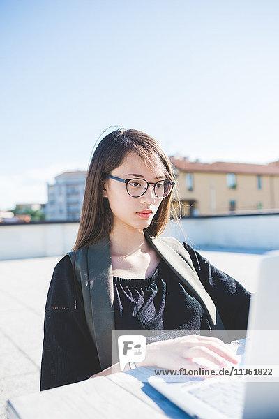 Junge Frau auf der Dachterrasse der Stadt beim Tippen auf dem Laptop