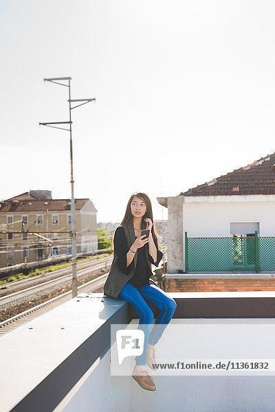 Junge Frau sitzt auf der Eckwand der Stadtdachterrasse mit Smartphone