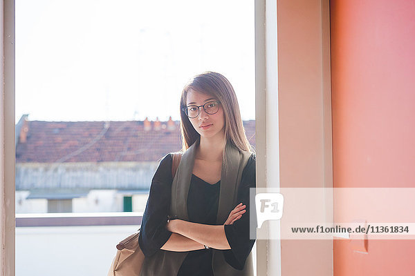 Porträt einer jungen Frau  die sich an die Tür der Dachterrasse lehnt