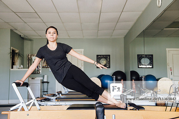 Woman in gym using pilates reformer