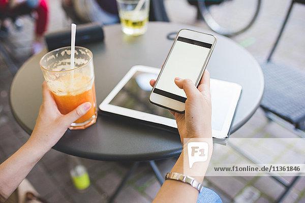 Abgetrennte Aufnahme der Hände einer jungen Frau mit einem Smartphone im Straßencafé