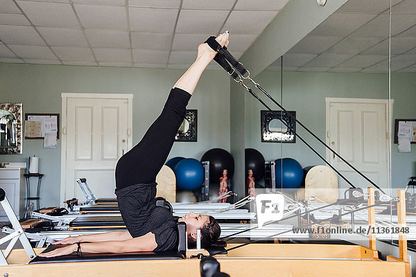 Side view of woman in gym using pilates reformer