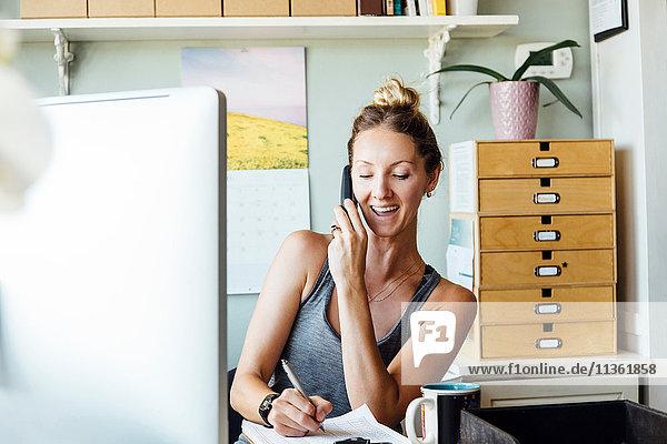 Frau im Büro beim Telefonieren  Schreiben