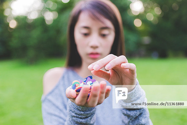 Young woman in park holding a handful of confetti