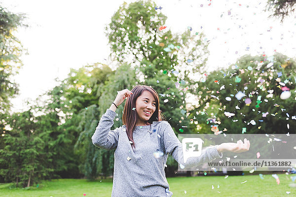 Young woman in park throwing confetti