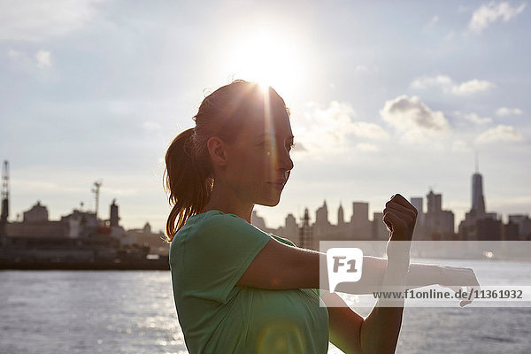 Woman by water stretching arm  Manhattan  New York  USA
