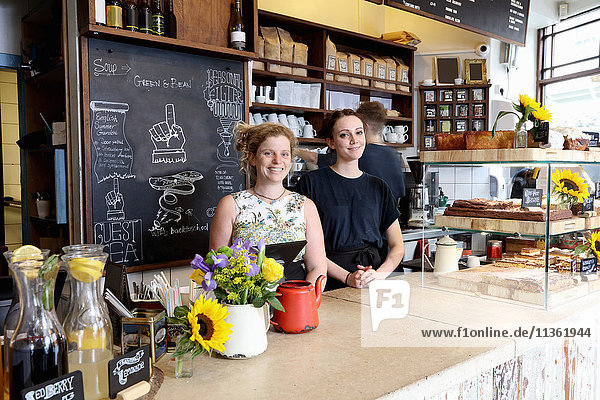 Colleagues at counter in coffee shop looking at camera smiling