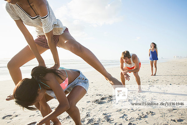 Young man and three female friends playing leapfrog on beach  Cape Town  South Africa