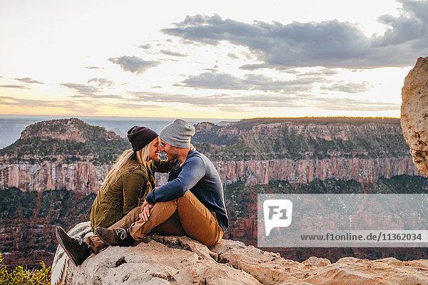 Couple sitting nuzzling on edge of Grand Canyon  Arizona  USA