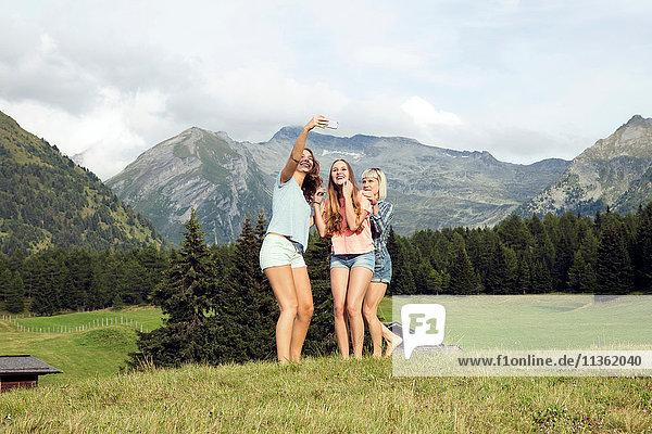 Three adult female friends taking smartphone selfie in Austrian Alps  Sattelbergalm  Tirol  Austria