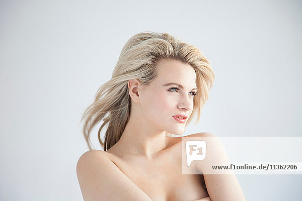 Studioporträt einer schönen blonden jungen Frau mit nackten Schultern