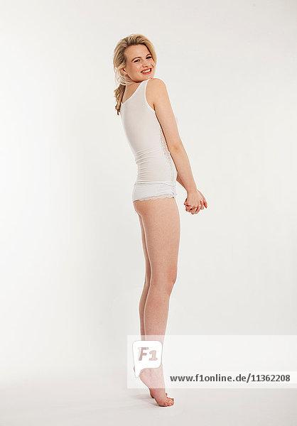 Studioporträt einer schönen blonden jungen Frau auf den Zehenspitzen stehend in Weste und Schlüpfer
